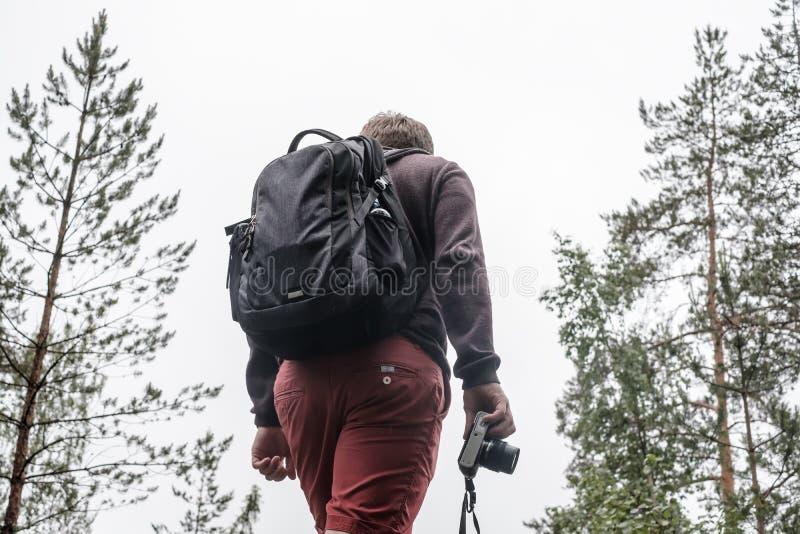Een mannelijke toerist met een rugzak en een camera in zijn hand bevindt zich op de bovenkant van een heuvel, tegen de achtergron royalty-vrije stock foto's