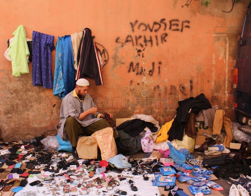 Een Marokkaanse zitting in een straat van oude stad van Marrakech met zijn goederen royalty-vrije stock foto
