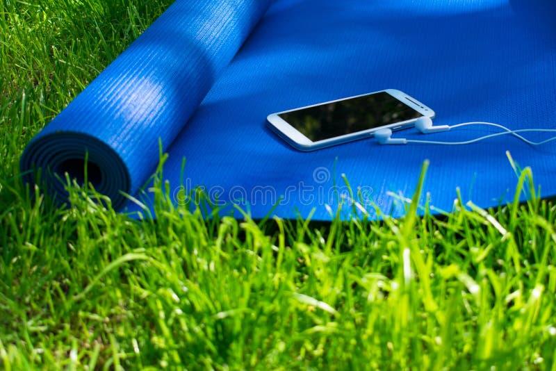 Een mat voor yoga en pilates, een telefoon met hoofdtelefoons en op groen gras, stock fotografie
