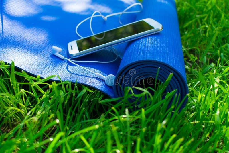 Een mat voor yoga en pilates, een telefoon met hoofdtelefoons en op groen gras, royalty-vrije stock afbeeldingen