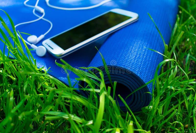 Een mat voor yoga en pilates, een telefoon met hoofdtelefoons en op groen gras, royalty-vrije stock foto's