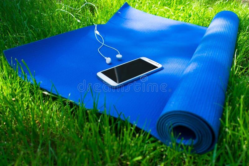 Een mat voor yoga en pilates, een telefoon met hoofdtelefoons en op groen gras, stock foto