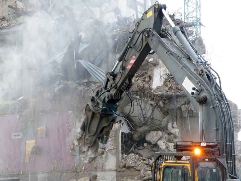 Een mechanische graver met een pneumatisch hamer tearing beneden en oud gebouw op een stedelijke ontwikkelingsplaats met stofpuin stock afbeeldingen
