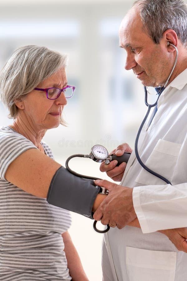 Een medische arts neemt een geduldige bloeddruk van s stock afbeeldingen