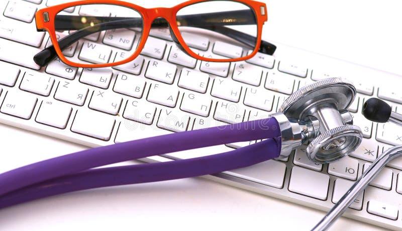 Een medische stethoscoop dichtbij laptop op lijst, aangaande wit stock fotografie