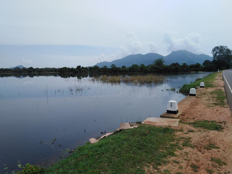 een meer dichtbij de weg en het meer door berg wordt gebeëindigd die royalty-vrije stock fotografie