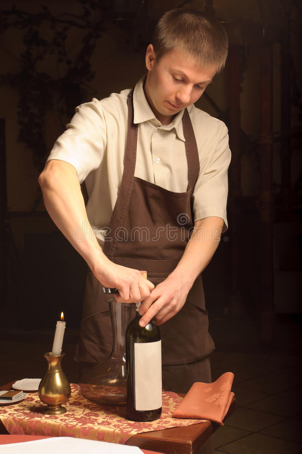 Een meer sommelier het openen wijnfles royalty-vrije stock afbeelding