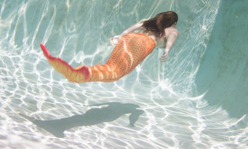 Een meermin met en een oranje staart onderwater stock fotografie
