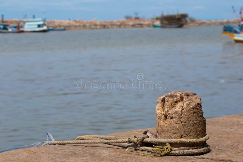 Een meertros op een dok in een haven houdt een oude visserijtreiler gebonden royalty-vrije stock foto's