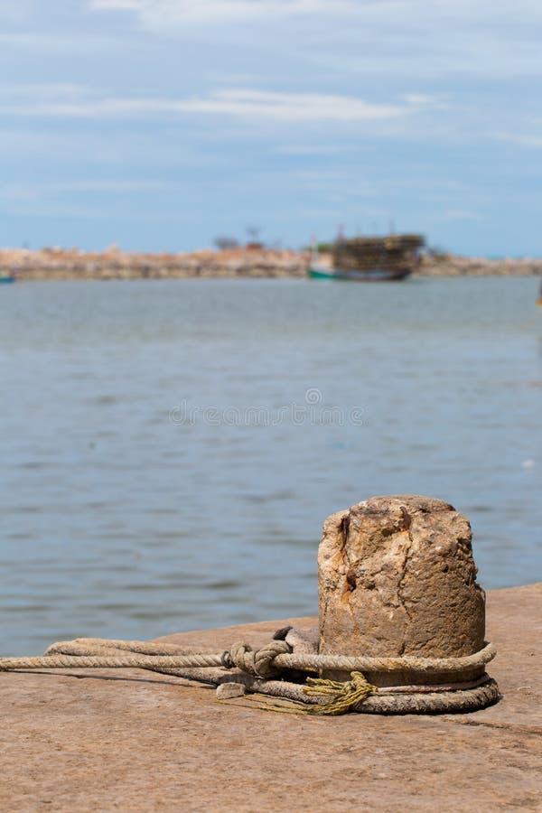 Een meertros op een dok in een haven houdt een oude visserijtreiler gebonden royalty-vrije stock afbeelding
