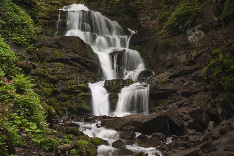 Een meeslepende waterval breekt zijn wateren tegen scherpe stenen stock foto