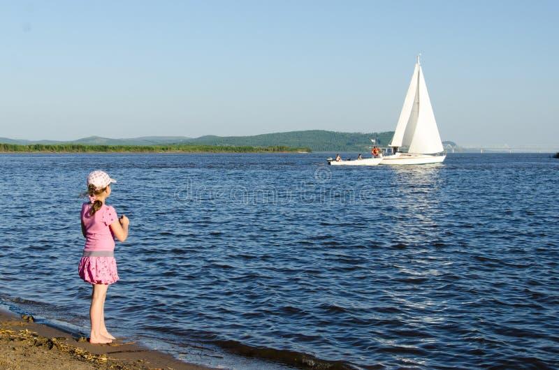 Een meisje bekijkt de drijvende witte varende boot stock fotografie