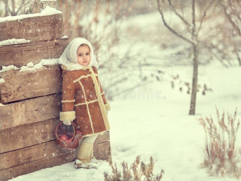 Een meisje bevindt zich bij een omheining in de winter stock fotografie