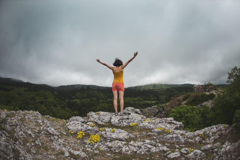 Een meisje bevindt zich bovenop een berg stock afbeeldingen