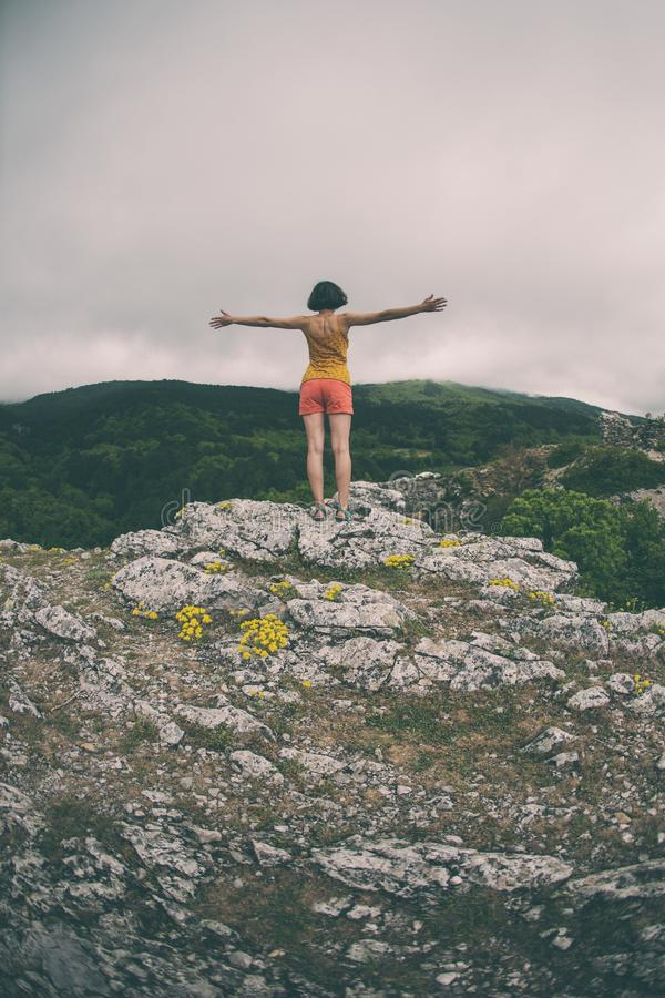 Een meisje bevindt zich bovenop een berg stock foto