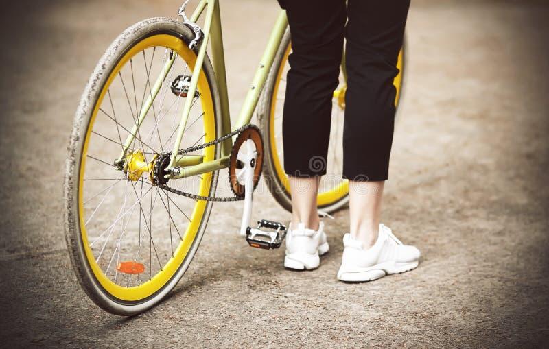 Een meisje bevindt zich dichtbij haar mooie fiets is geelgroen royalty-vrije stock foto's