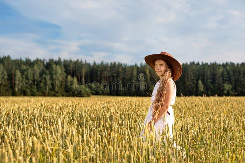 Een meisje bij het tarwegebied in een cowboyhoed stock foto