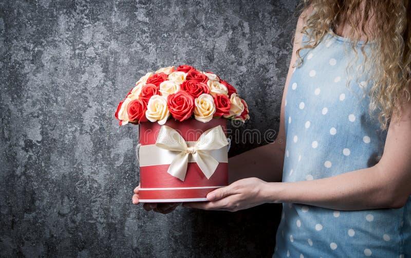 Een meisje in een blauwe kleding houdt een boeket van rode en witte rozen in een hoedendoos Donkergrijze achtergrond stock afbeeldingen