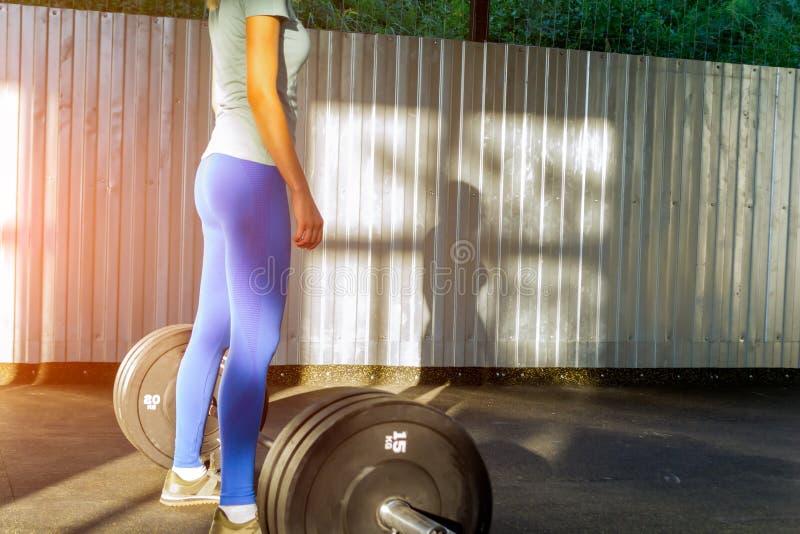 Een meisje in een blauwe T-shirt en legging bevindt zich binnen in een open gymnastiek voor royalty-vrije stock foto's