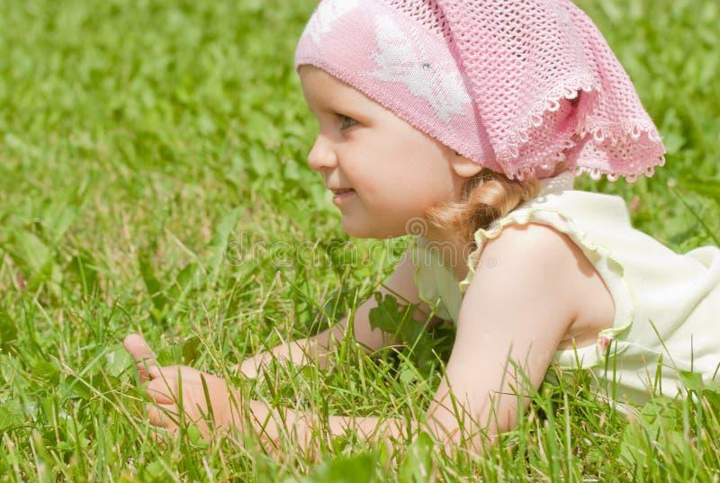 Een meisje dat op een groen gazon ligt stock foto