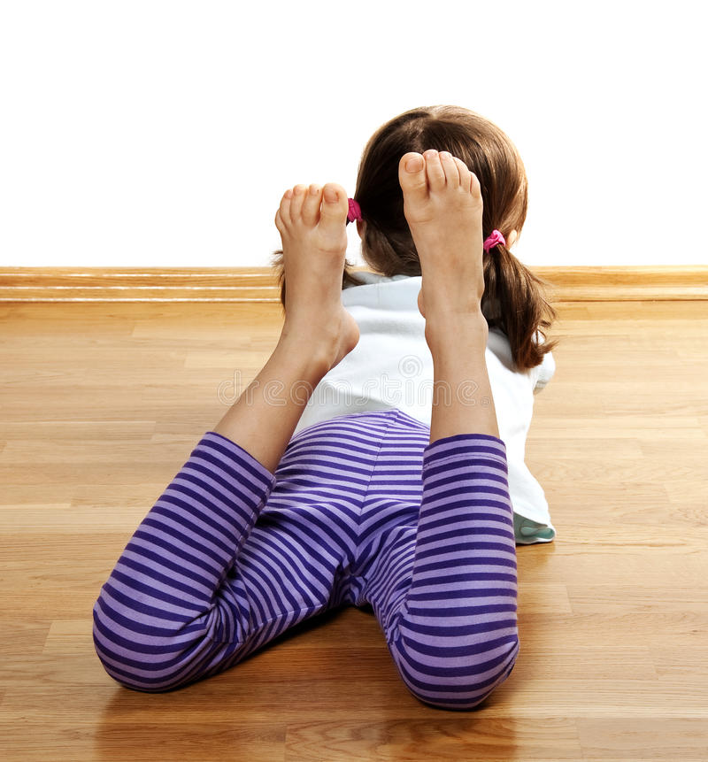 Een meisje dat op een houten vloer rust royalty-vrije stock fotografie