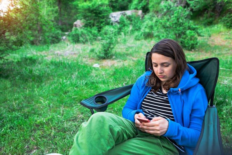Een meisje in de aard kijkt in een mobiele telefoon royalty-vrije stock fotografie