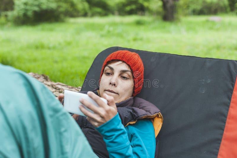 Een meisje in de aard kijkt in een mobiele telefoon stock fotografie