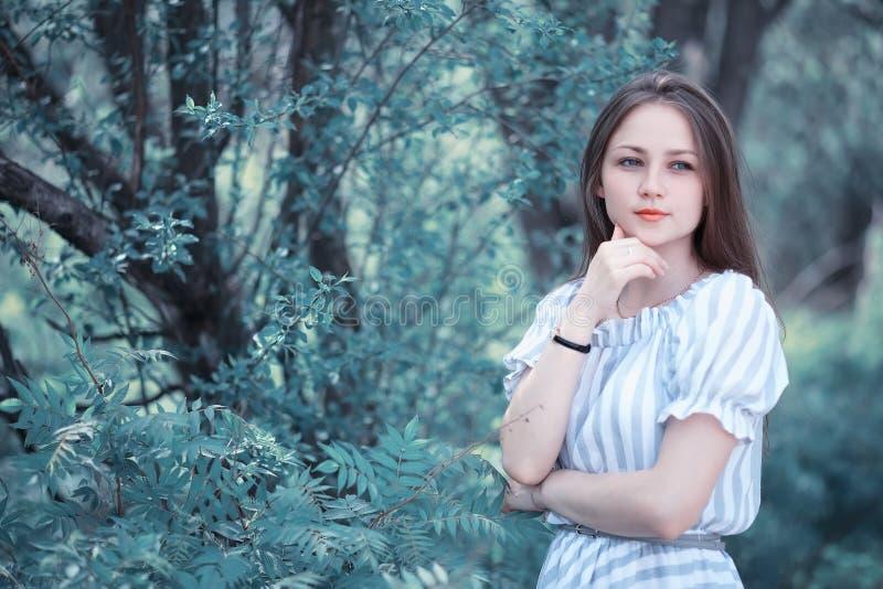 Een meisje in een de lente groen park stock afbeeldingen