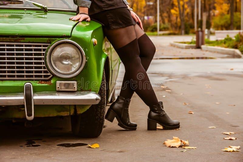 Een meisje in een denimjasje en zwarte kousen, de nylonkousen en een zwarte rok leunen over de groene retro auto benenclose-up royalty-vrije stock fotografie