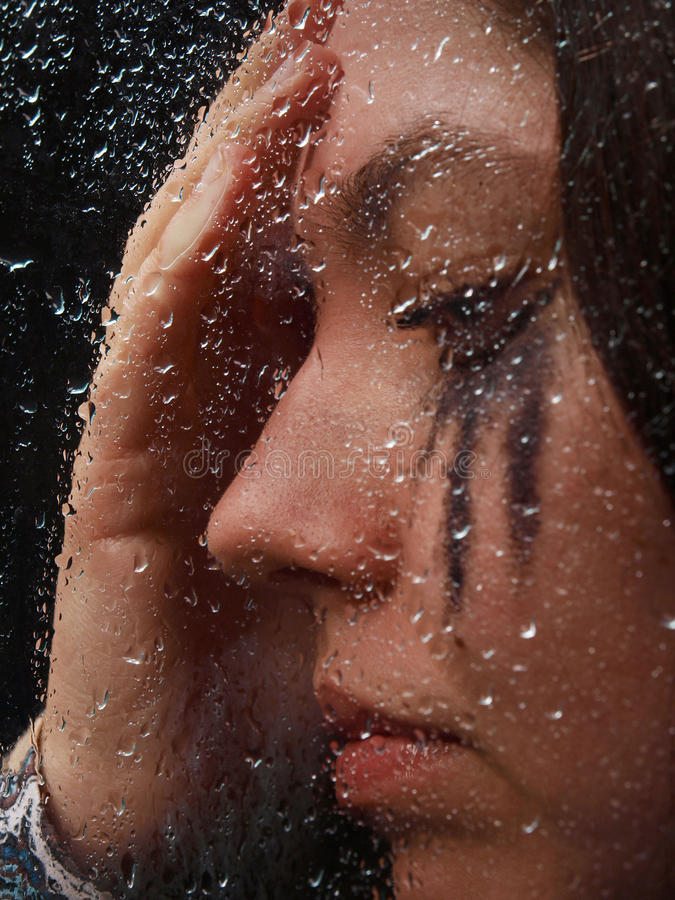 Een meisje denkt standind achter het glas op één van regenachtige dag royalty-vrije stock afbeelding