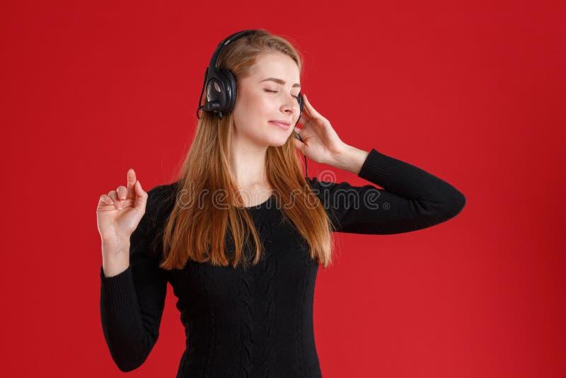Een meisje die, die aan muziek in hoofdtelefoons luisteren en van het genieten met haar gesloten ogen Op een rode achtergrond stock foto's