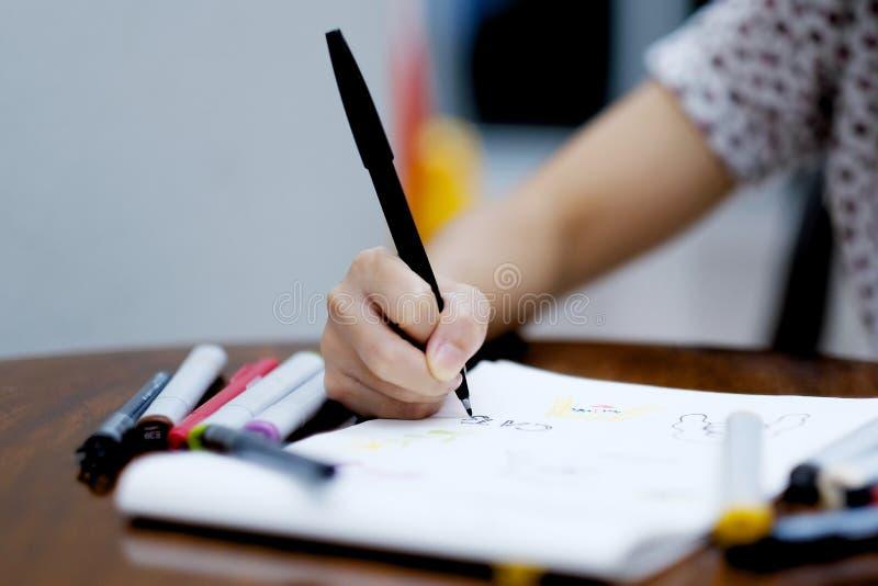 Een meisje die een beeld trekken op Witboek door zwarte pen royalty-vrije stock fotografie