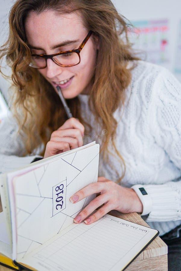 Een meisje die bij haar bureau werken royalty-vrije stock afbeelding