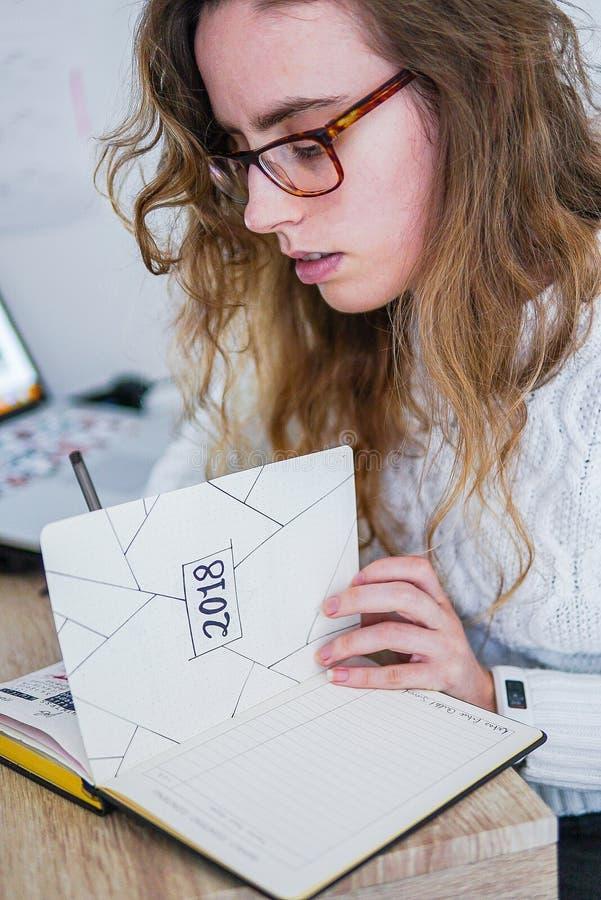 Een meisje die bij haar bureau werken royalty-vrije stock afbeeldingen