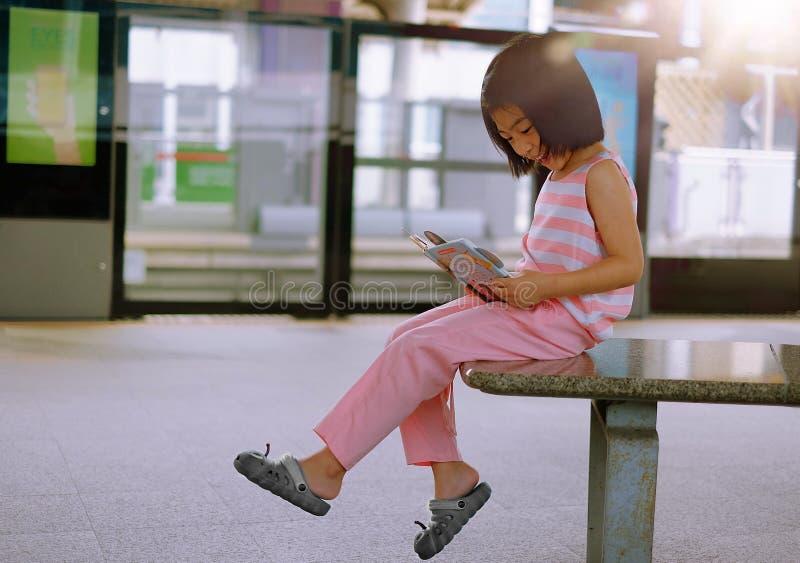 Een meisje die een boek lezen bij een station royalty-vrije stock foto's