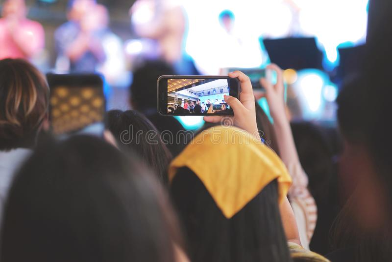 Een meisje die haar smartphone gebruiken voor neemt een beeld in muziekoverleg royalty-vrije stock afbeelding