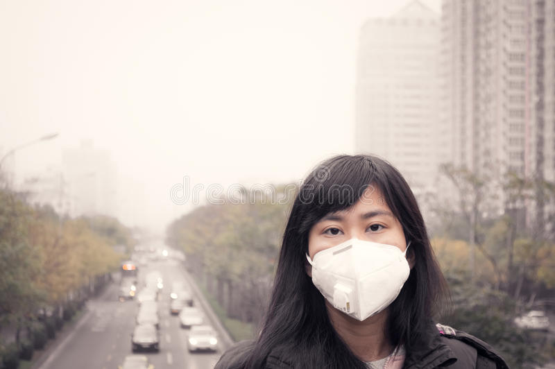 Een meisje die mondmasker dragen tegen luchtvervuiling royalty-vrije stock foto