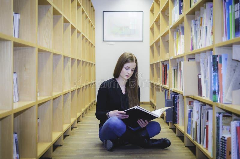 Een meisje die op de bibliotheekvloer situeren stock afbeelding