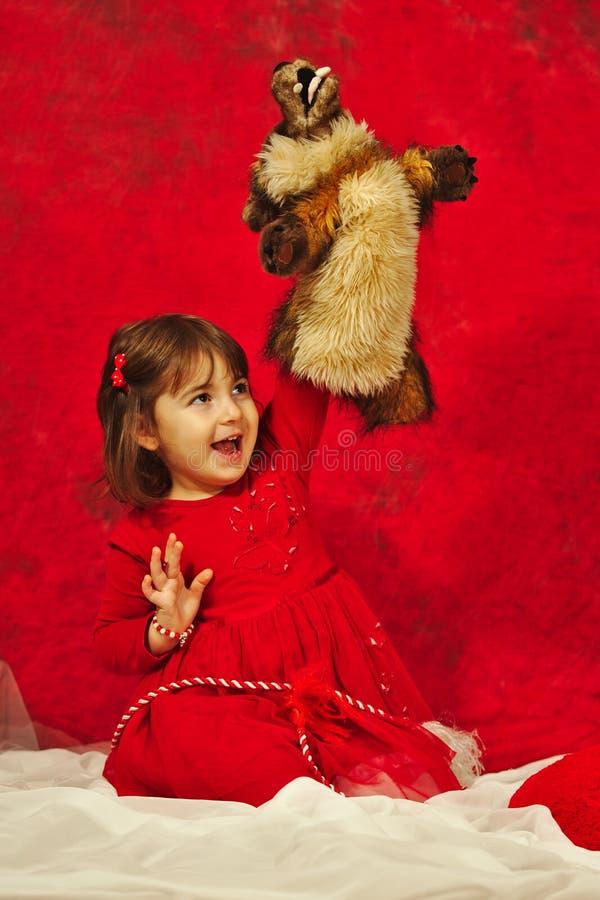 Een meisje die in rood een kleine slechte wolfsmarionet koesteren royalty-vrije stock afbeeldingen