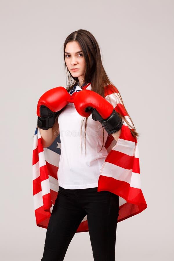 Een meisje die terwijl status in bokshandschoenen en behandeld met een Amerikaanse vlag stellen royalty-vrije stock afbeelding