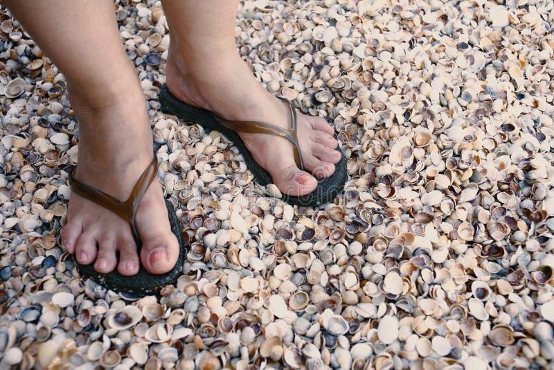 Een meisje die zich op het strand in wipschakelaars bevinden stock foto's