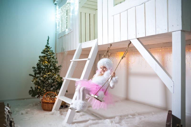 Een meisje in een doggie slingert op een schommeling bij de voorgevel van een wit die blokhuis voor Kerstmis en Nieuwjaar wordt v royalty-vrije stock foto's
