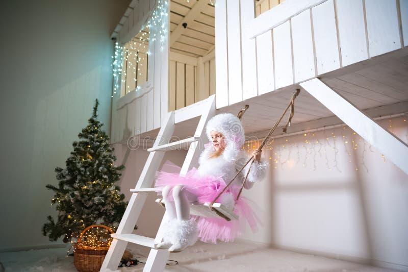 Een meisje in een doggiekleding op een schommeling bij de voorgevel van een wit die blokhuis voor Kerstmis en Nieuwjaar wordt ver royalty-vrije stock afbeelding