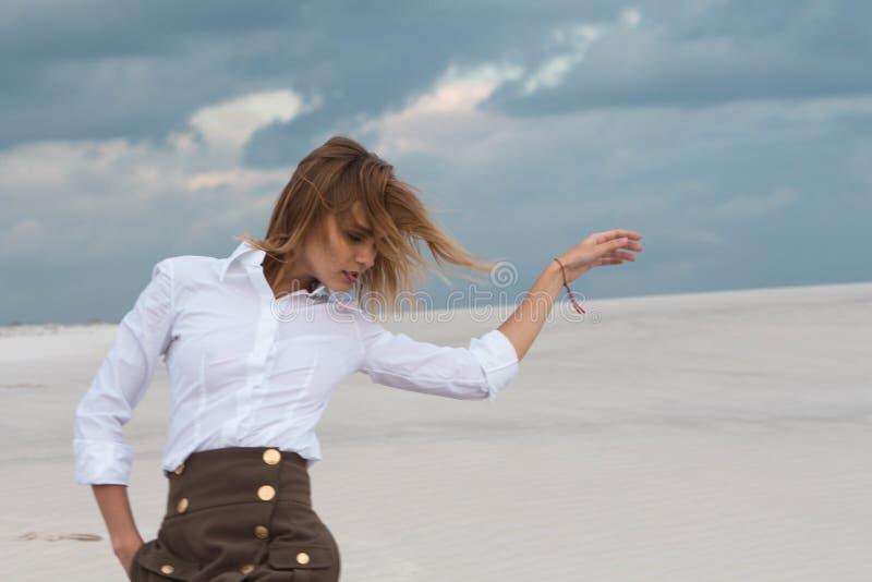 Een meisje door de wind in de woestijn wordt meegesleept die royalty-vrije stock foto's