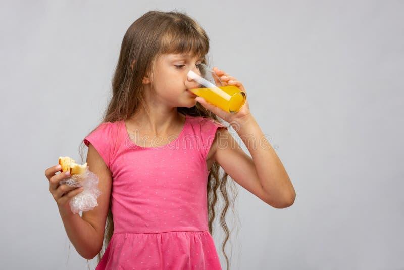Een meisje drinkt jus d'orange en eet een broodje royalty-vrije stock afbeelding