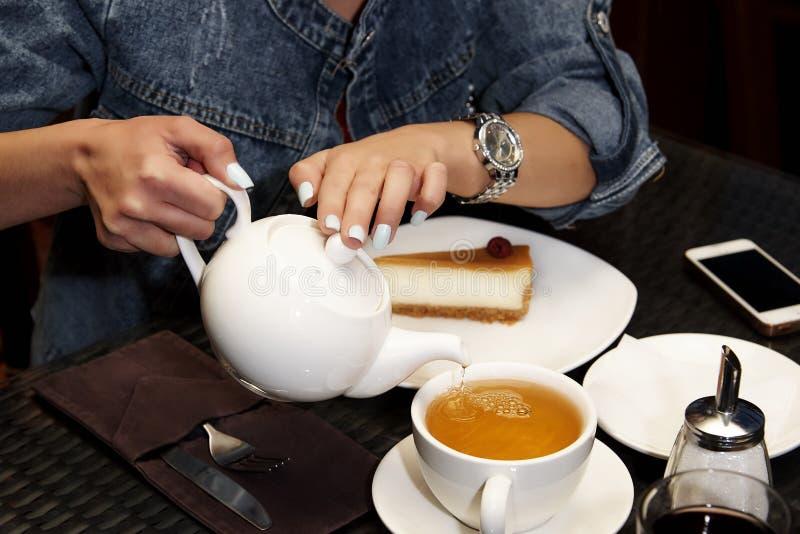 Een meisje drinkt thee met een kaastaart stock afbeeldingen
