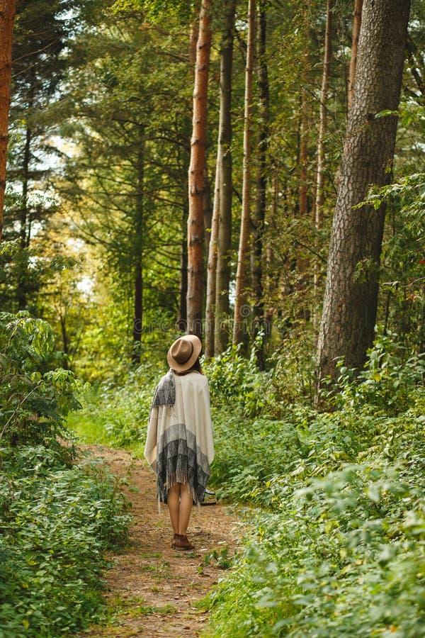 Een meisje in een poncho en een hoed in bos stock foto