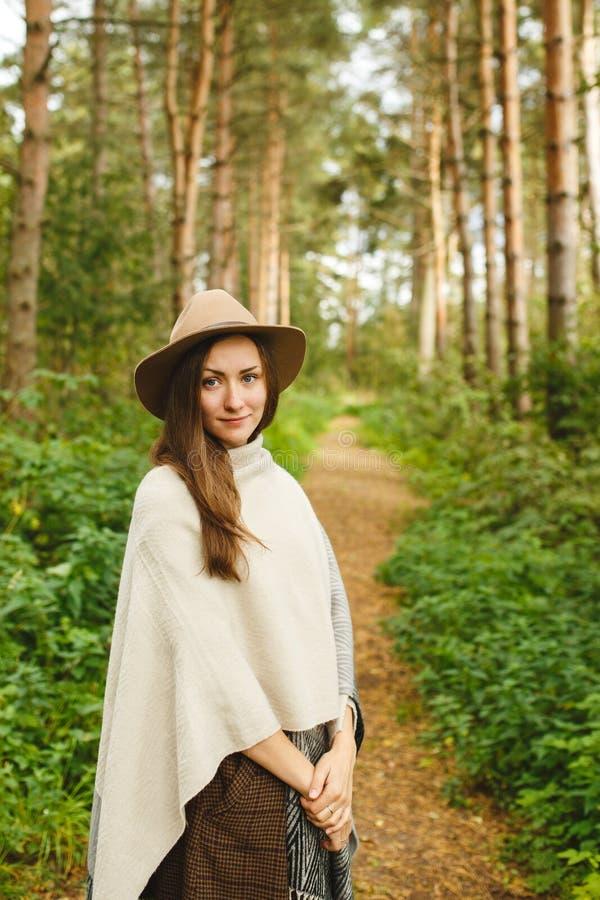 Een meisje in een poncho en een hoed in bos stock afbeelding