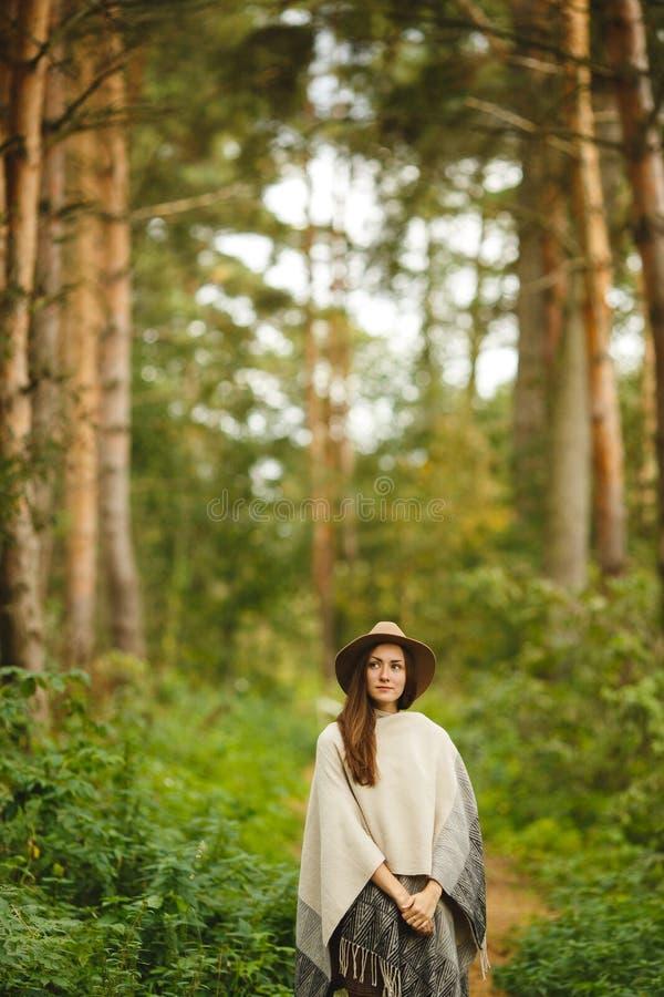 Een meisje in een poncho en een hoed in bos stock afbeeldingen