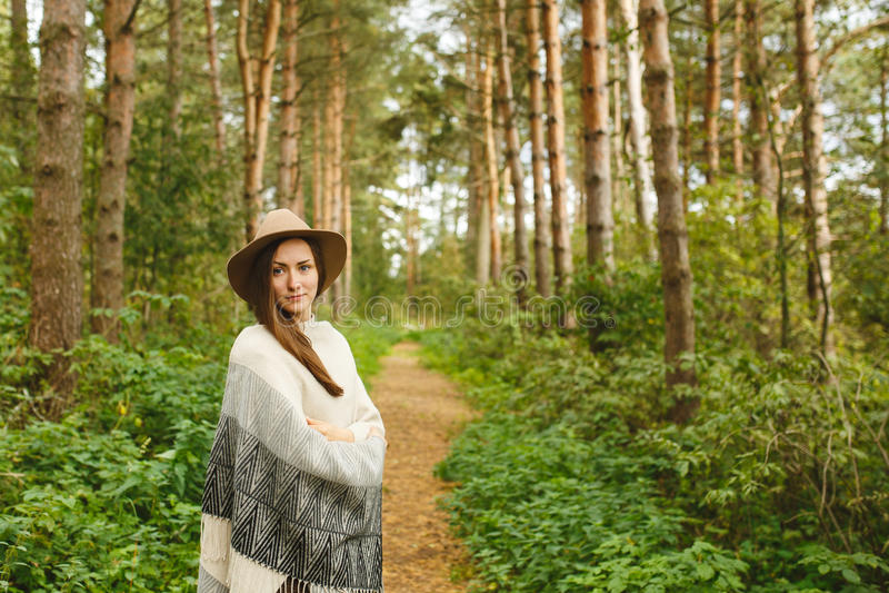 Een meisje in een poncho en een hoed in bos royalty-vrije stock fotografie